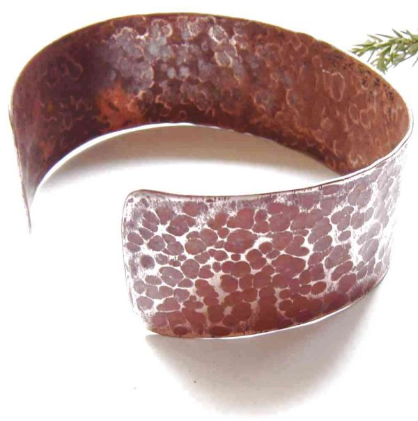 Hammered Copper Wide Cuff Bracelet. An oval, bangle style bracelet, handcrafted in copper, and Made in Britain. I hand-forge this copper wrist band, giving it a textured, hammered surface pattern which gives the bracelet an aged or rustic appearance, whilst making each bracelet unique and emphasising its handmade nature. Handmade in Britain, in the north-east of England.