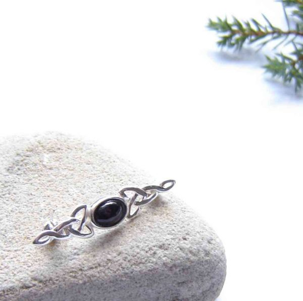 Handcrafted Whitby Jet Celtic Brooch. A small brooch or scarf pin in black, natural British gemstone. This black jet is from the North Yorkshire coast of England. Whitby is also historically in Northumbria. I handcraft the jet into a tiny, oval cabochon, using lapidary (stonecutting) techniques, to set in this Celtic style sterling silver brooch.