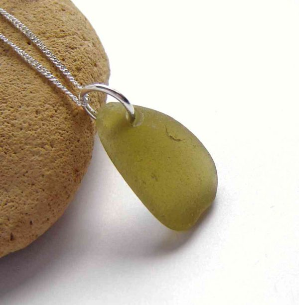 Light Olive Northumbrian Sea Glass Necklace. A pale olive green sea glass pendant necklace which I have handmade with genuine English sea glass. This sea glass is roughly triangular, shaped naturally by the tumbling action of the North Sea, off the coast of Britain, and washed up on its shores, where I have collected the sea glass by hand.