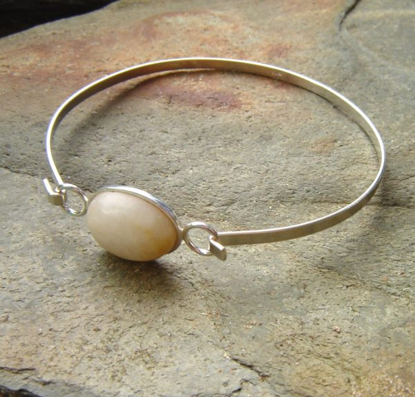 Natural British Quartz Sterling Silver Bracelet. A torc bracelet in natural creamy white and amber British quartz. I have collected this quartz by hand in the lovely Northumbria region of England, in the United Kingdom. I have handcrafted the natural stone into an oval cabochon to set in this sterling silver bangle. Natural Stone Bracelets from Northumbria Gems.