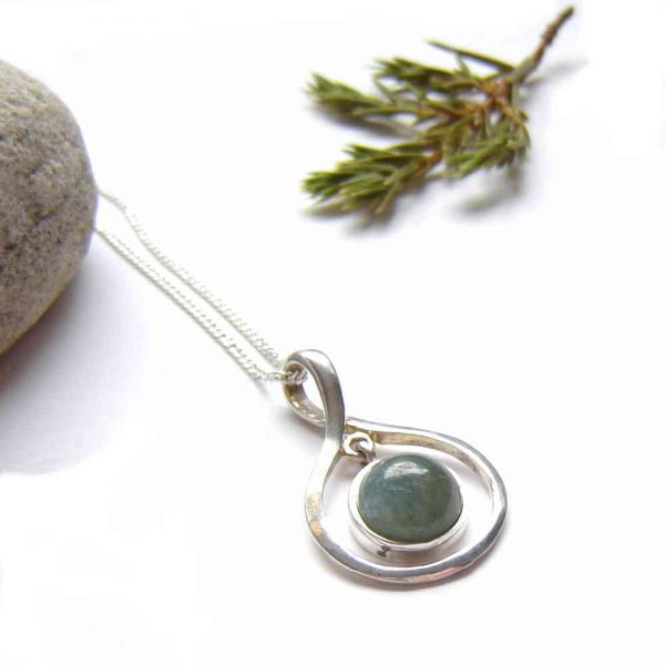 Natural Green Apatite Drop Necklace. A green gemstone drop pendant necklace in a contemporary 925 sterling silver double mount. This apatite necklace has a sterling silver tear drop outer mount with a cabochon drop on the inside. The pendant is made with semi-opaque natural apatite gemstone, found on the Northumbrian coast of England.