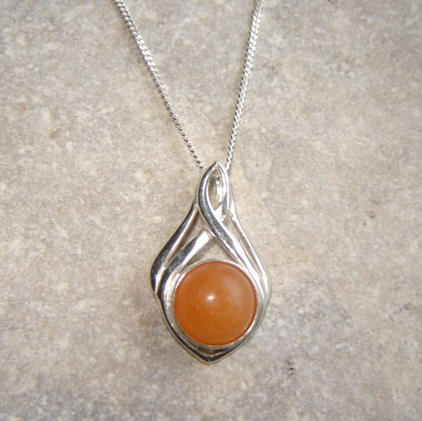 Orange Natural Carnelian Pendant. English carnelian cabochon pendant in a sterling silver mount. This carnelian has been hand-collected on the Northumbrian coast of England, and is natural and untreated.