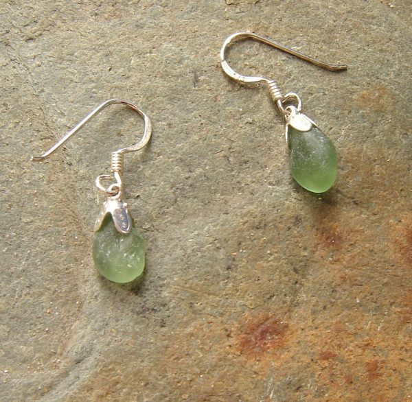 Green Northumbrian Sea Glass Earrings. These small sea glass earrings are handmade with pieces of genuine green sea glass found on the Northumbrian coast of England, set in sterling silver. English sea glass earrings with 925 sterling silver bell caps and wires.