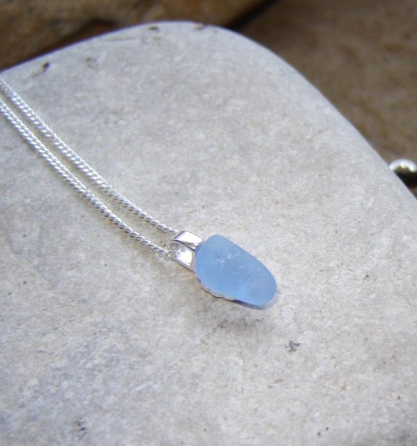 Tiny Light Cobalt Blue Sea Glass Pendant. Tiny Northumbrian Sea Glass necklace in light cobalt blue sea glass on a sterling silver curb chain.